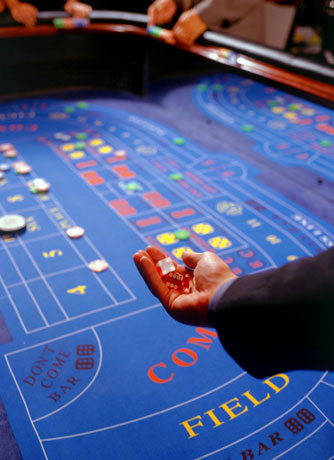 Craps table hand with dices